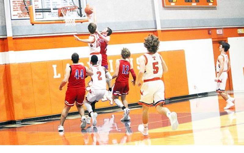 Teague's Waylon Allison (12) blocks a shot by an Elkhart player during the opening District 20-3A game Friday night. Teammate Ty Abram (2) moves in for a possible rebound and Teague's Jarrett Bodine (5) also runs downcourt attempting to get in on the play. Photo by Skip Leon/For the Teague Chronicle