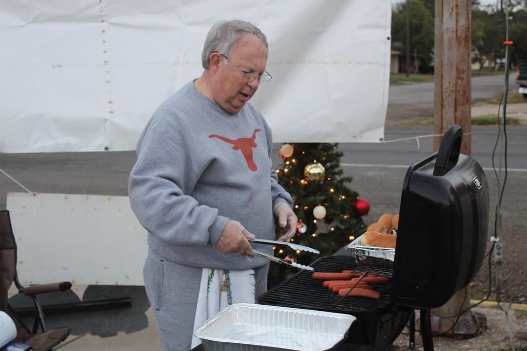 Bill David Bowers grills hot dogs to serve at the fundraiser for Teague's Christmas in the Parks.